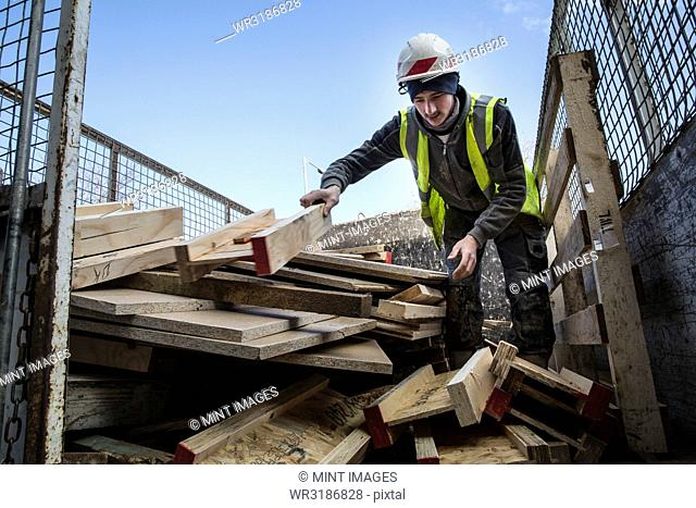 Young man wearing hard hat and reflective vest standing on top of stack of recycled wood