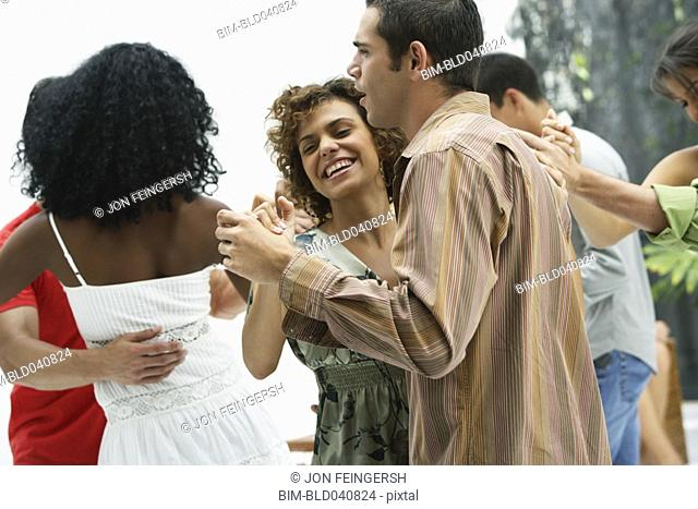 South American couples dancing at party