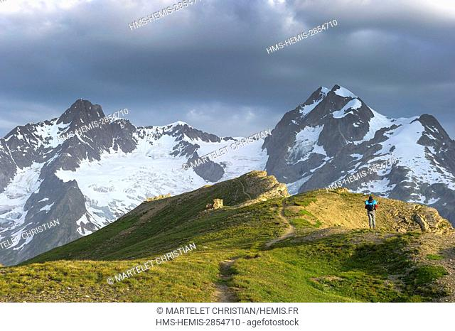 Italy, Valle d'Aosta, Val Veni, hiker walking on the ridges of Mont Fortin (2811m) with in the backgrond the Aiguille des Glaciers (3816m) on the left and the...
