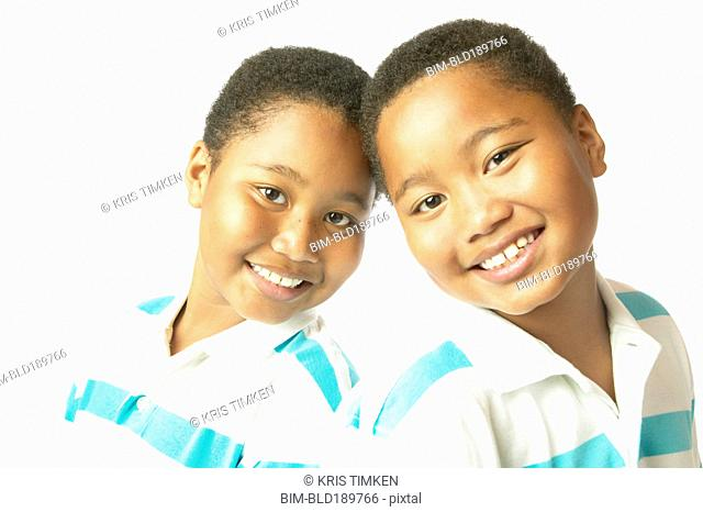 Studio shot of young African twin brothers smiling