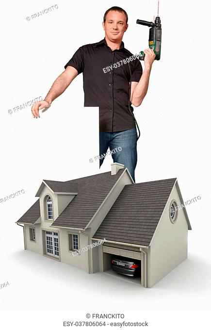 Handyman holding a drill and a blank sign by a model house