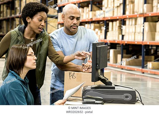 A group of three mixed race warehouse workers checking inventory on a computer in a large distribution warehouse