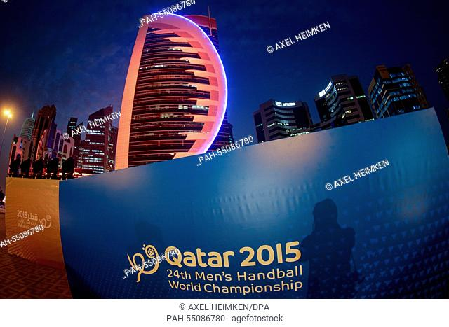 An advertising banner for the Handball World Championship is pictured in front of the illuminated skyline of Doha during the men's Handball World Championship...