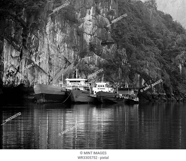 Boats Docked by a Cliff