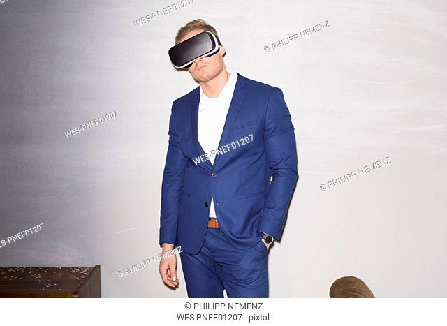 Young man wearing blue suit using Virtual Reality Glasses