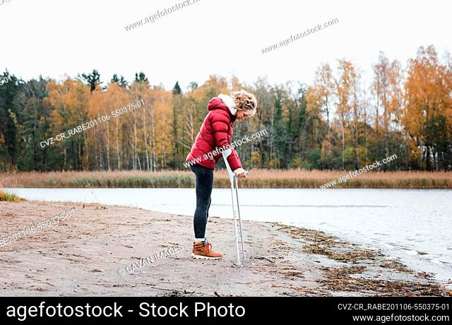 injured woman stood at the beach with crutches looking thoughtful