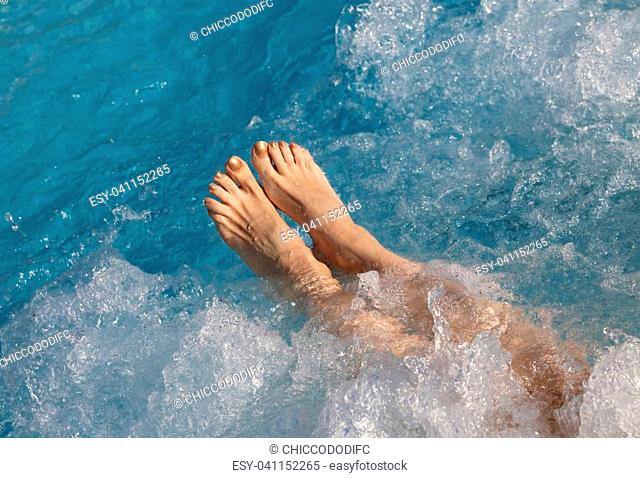 bare feet and legs of the young woman during hydro massage therapy in the spa pool