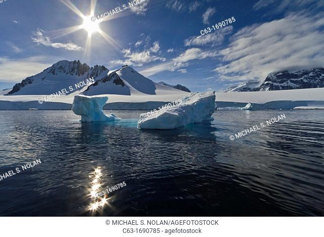 View of calm seas, icebergs, and reflected mountains surrounding Damoy Point from the National Geographic Explorer in Dorian Bay, Antarctica