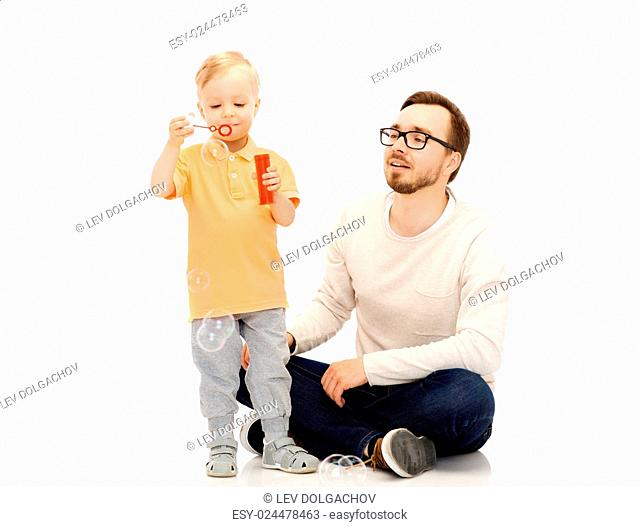 family, childhood, fatherhood, leisure and people concept - happy father and little son blowing bubbles and having fun