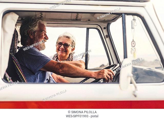 Senior couple traveling in a vintage van, taking a break at the sea, talking