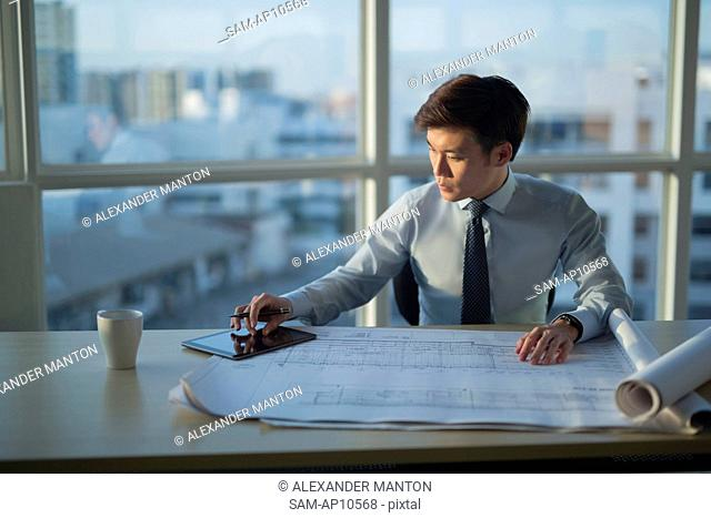 Singapore, Architect sitting at desk with architectural plans using digital tablet