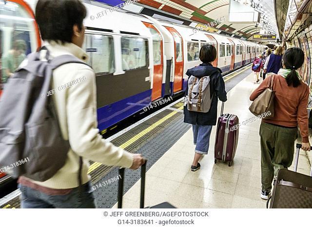 England, London, Soho, Piccadilly Circus Underground Station, subway tube, public transportation, platform, train, Asian, man, woman, rolling luggage