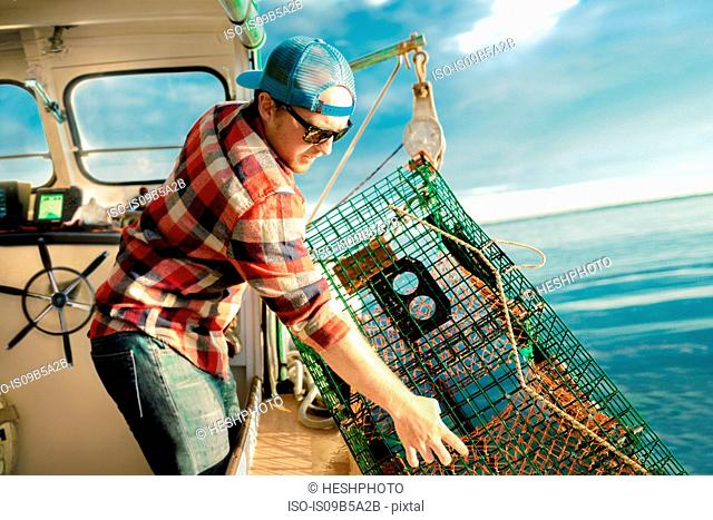 Young man lifting lobster cage from winch on fishing boat on coast of Maine, USA