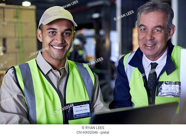 Portrait smiling manager and worker using laptop in distribution warehouse