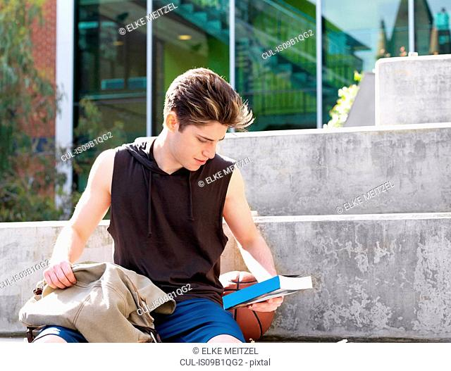 Young man sitting on step, outdoors, reading back of book