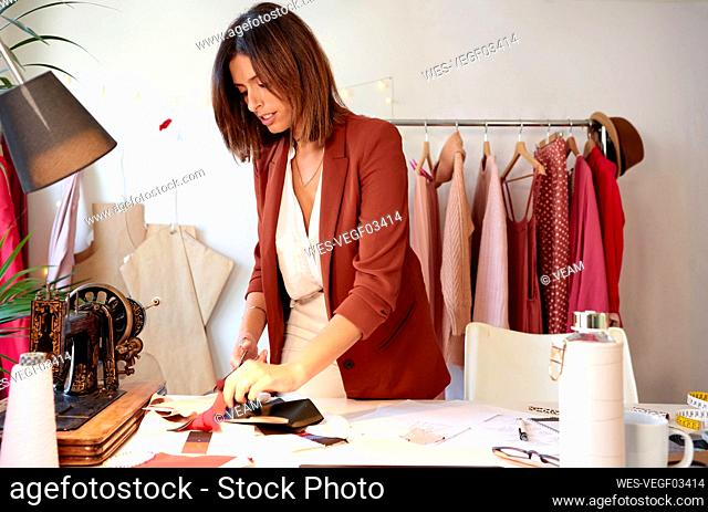 Female design professional cutting fabric swatch at desk against clothes rack