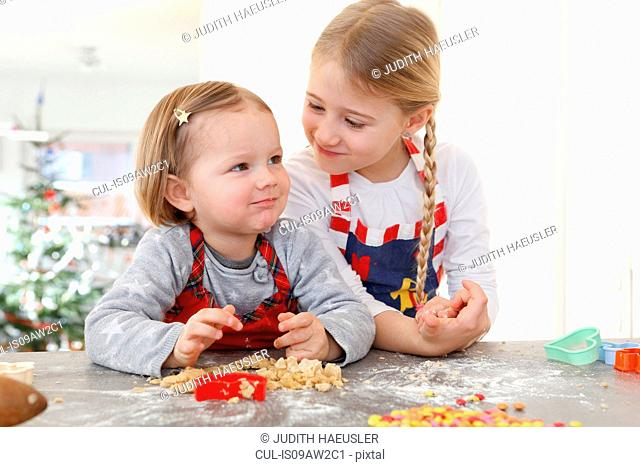 Sisters at kitchen counter making cookies smiling