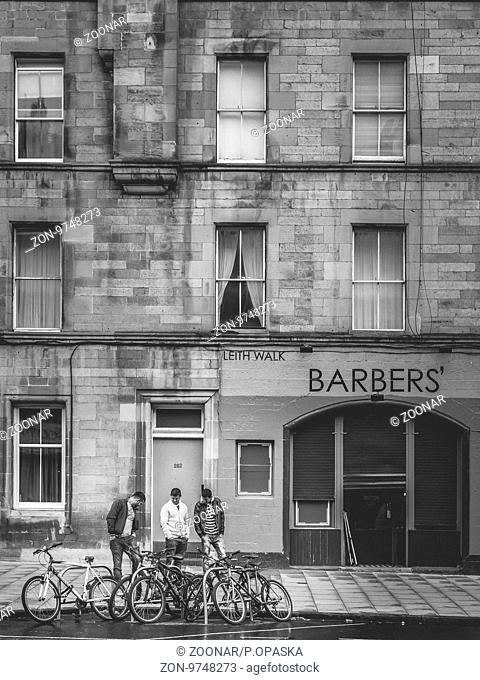Edinburgh, Scotland - 02 September 2016 : Three man looking at parked bicycles in front of a barber shop in Leith in Edinburgh, Scotland
