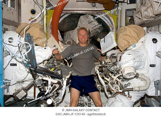 Astronaut Tim Kopra, Expedition 20 flight engineer, is pictured between two Extravehicular Mobility Unit (EMU) spacesuits in the Quest airlock of the...