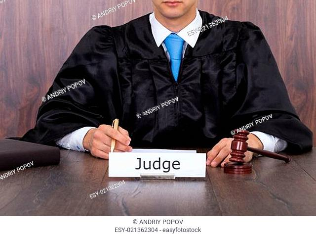 Judge With Mallet Sitting At Desk