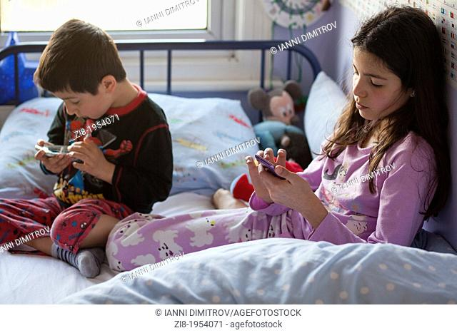 Children playing games on mobile devices in bed