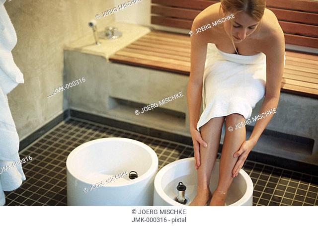 Young woman taking, having, a footbath
