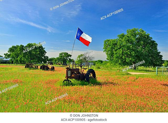 Texas flag on a 1935 John Deer tractor in a field of paintbrush, Burnet County, Texas, USA