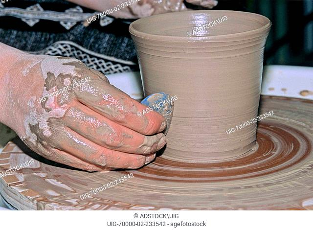 A potters hands working a clay pot close up