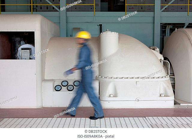 Mature construction worker walking through power station, blurred motion