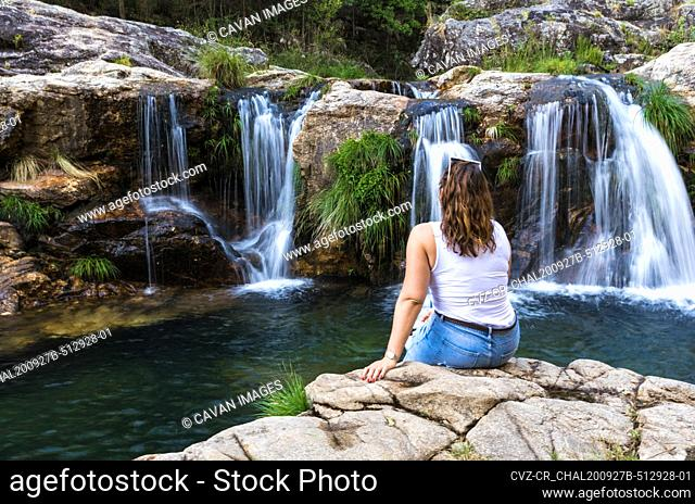 Young woman looking at the waterfall in the forest