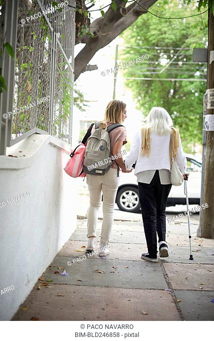 Grandmother and granddaughter holding hands and walking in city