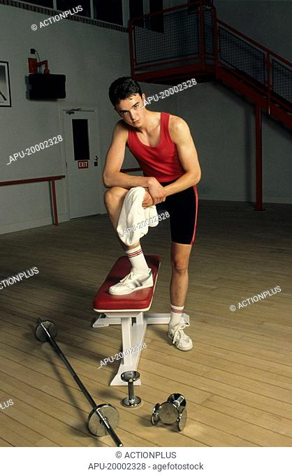 Young man in a gym with a bench and free weights