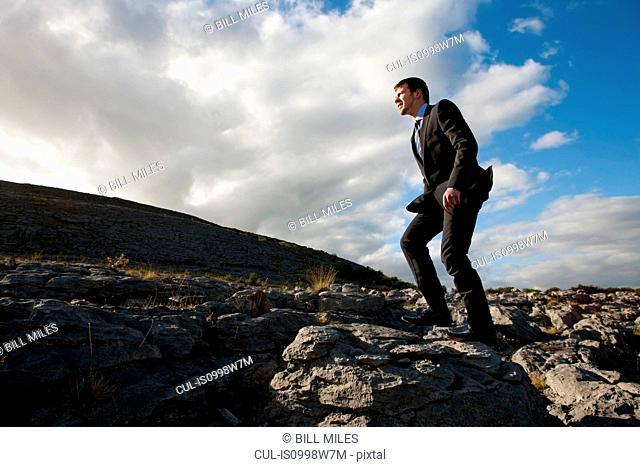 Businessman walking in remote, rock landscape
