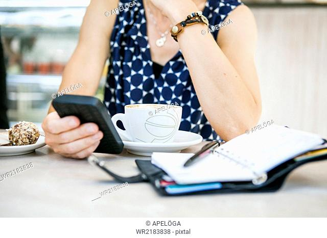 Midsection of mature woman using mobile phone with coffee and diary on table in cafe