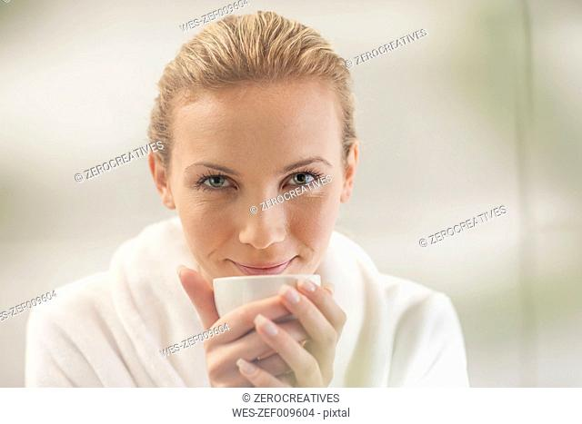 Portrait of smiling young woman in bathrobe drinking tea