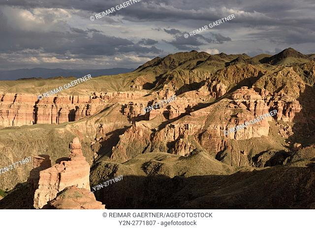Couple taking picture at sunset on top of Hoodoo at Charyn Canyon Kazakhstan