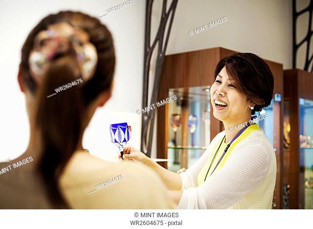 Saleswoman in a shop selling Edo Kiriko cut glass in Tokyo, Japan