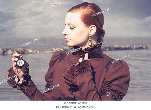 Young woman in a victorian dress standing alone outdoors beside the sea and holding a pocket watch in her hand