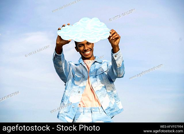 Smiling young man holding cloud while standing against sky