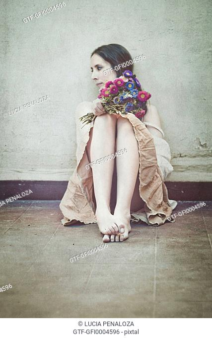 Young woman sitting on the patio holding flowers