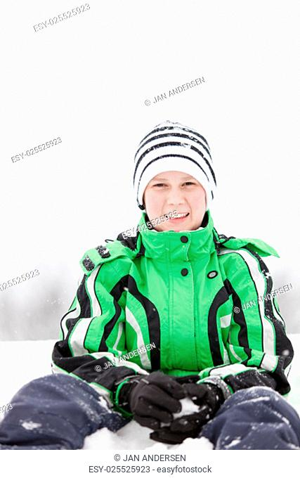 Young boy kneeling in the snow making snowballs in his gloved hands looking at the camera with a friendly smile, close up view in fresh white winter snow