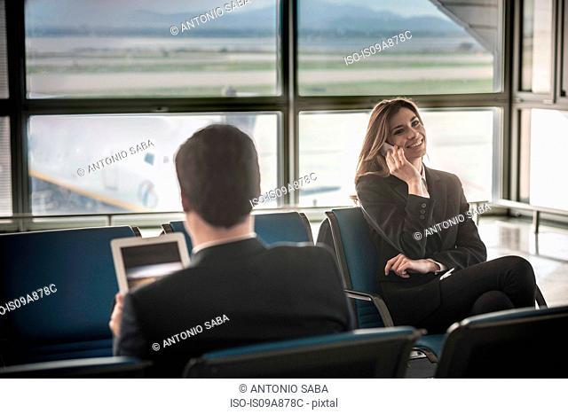 Businessman using digital tablet, businesswoman on mobile phone