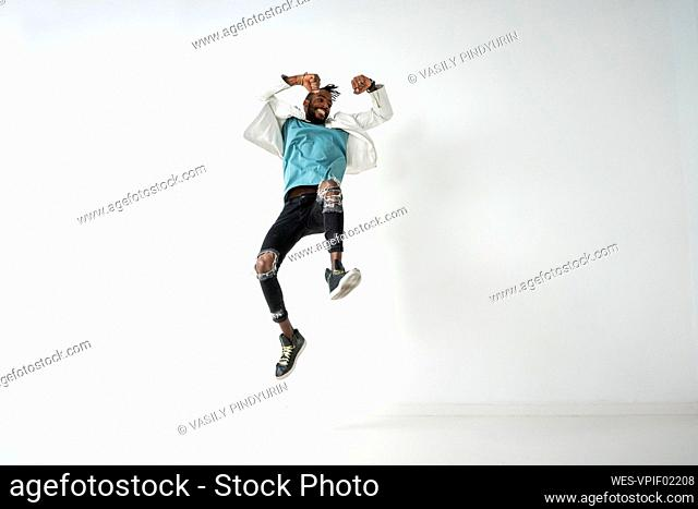 Young man jumping and dancing in front of white wall