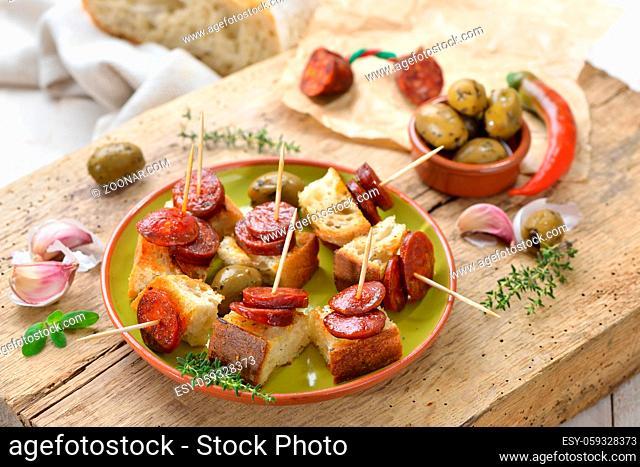 Spanische Pinchos: Angebratene scharfe Chorizo Paprikasalami auf geröstetem Weißbrot serviert ? Spanish snack: Fried Spicy chorizo sausage on roasted bread...
