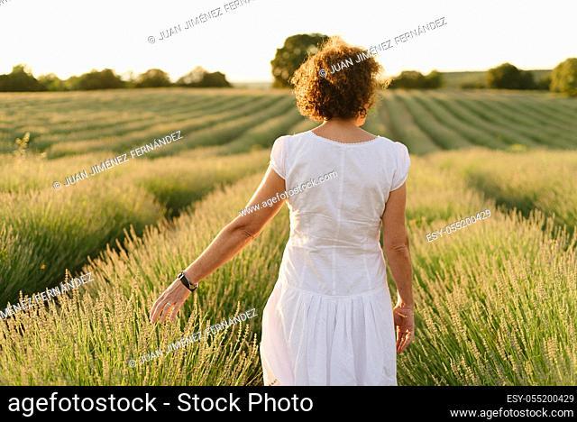 Beautiful woman in a white dress walks in the lavender field
