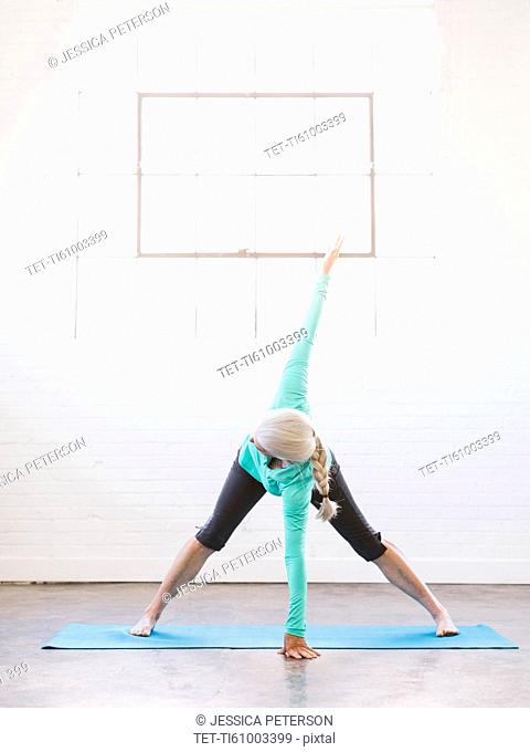 Senior woman practicing yoga on mat