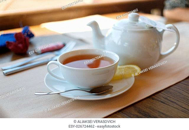 Cup of tea with lemon and teapot. Shallow depth of field