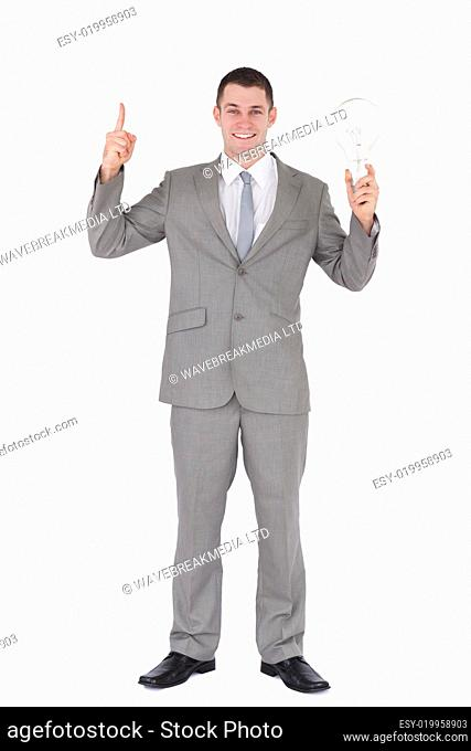 Portrait of a businessman holding a bulb and pointing at something