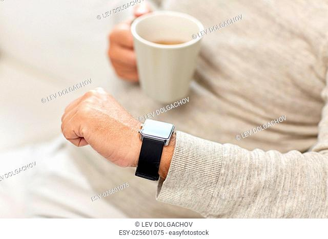 time, morning and people concept - close up of senior man with cup of tea looking at wristwatch at home