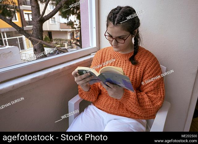 little teenager girl with hair in plaits reading a book in balcony in quarantine days